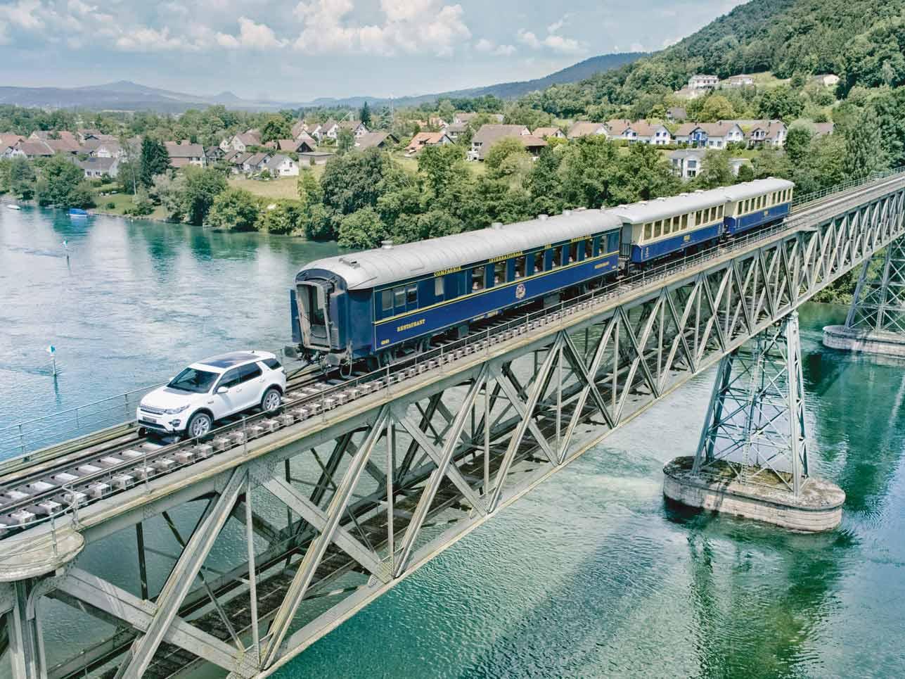 So etwas sieht man auch nicht alle Tage: Ein Land Rover Discovery Sport fährt über eine Eisenbahnbrücke, die den Rhein überspannt, und zieht dabei drei Waggons mit einem Gesamtgewicht von 100 Tonnen hinter sich her.